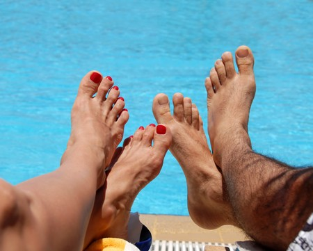 boy feet: male and female feet by blue swimming pool