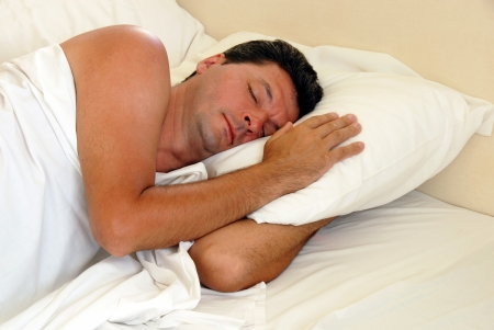 mature man sleeping on white pillow in bed