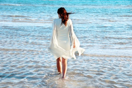 wind down: woman in white dress and raised hands walking in blue sea water