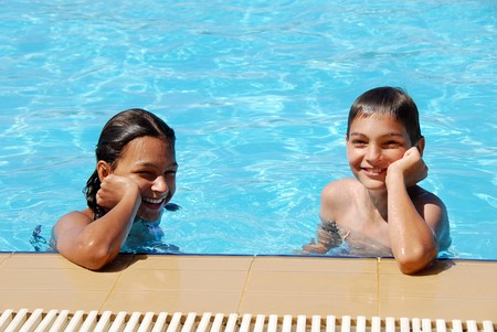 smiling girl and boy in blue swimming pool portrait photo