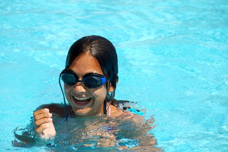 happy teen girl with goggles blue swimming pool portrait photo