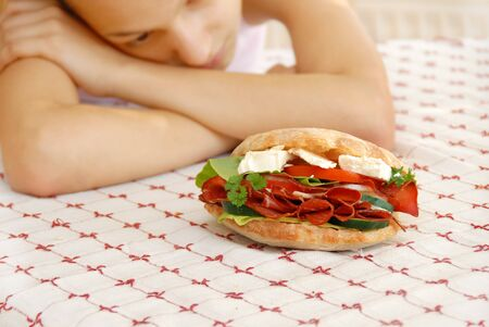 abstinence: hungry girl hands teen girl by appetizing big sandwich with ham and cheese