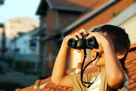 closer: teen boy watching at black binoculars outdoor portrait