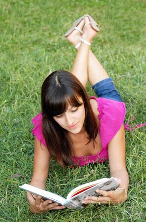 young woman lying reading a book in grass outdoor photo