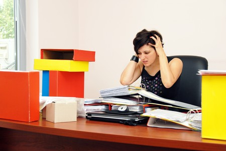 despaired stressed woman sitting at desk overloaded with work holding her head Stock Photo - 8167893
