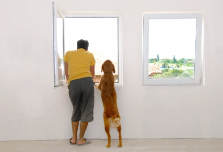 man and his dog looking through window back view photo