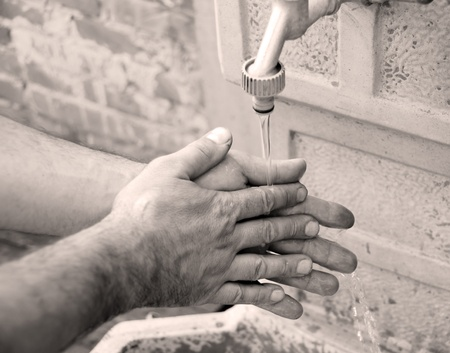 man washing hands outdoor in yard in black and white technique photo