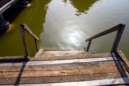 spunk: old shabby wooden staircase on green Palic lake, Serbia Stock Photo