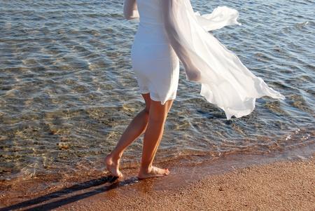 Wandelen door de zee op zand Stockfoto