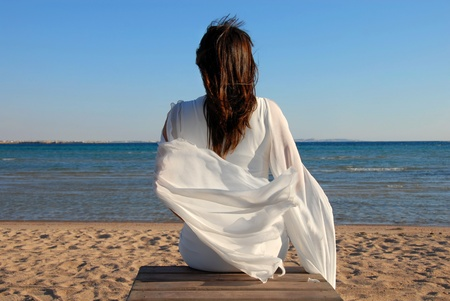 woman in white dress back sitting on beach by sea photo