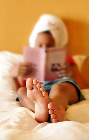relaxing teenage girl reading  book after shower focused on feet photo