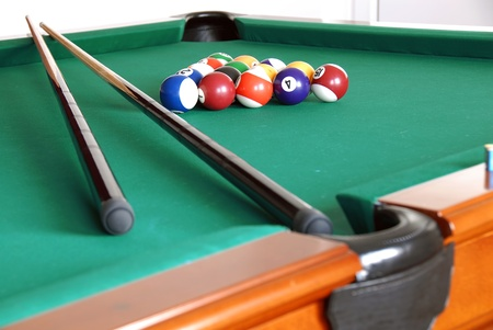 billiards green table with balls and two black cues photo