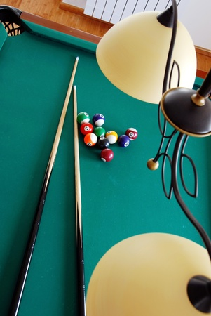 snooker cues: lamp over billiards green table with balls and two black cues