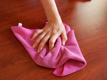 microfibra: limpiar la superficie de madera con trapo Rosa de mano Foto de archivo