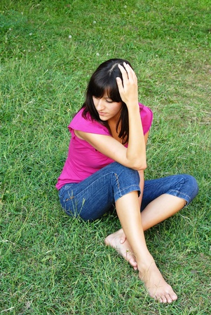 barefooted: young brunette woman on grass thinking outdoor Stock Photo