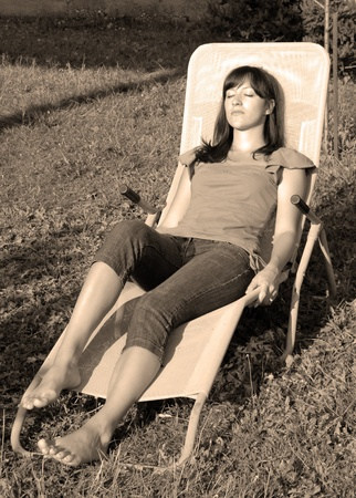 young woman relaxed in outdoor folding chair outdoor in black and white photo