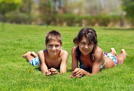 smiling boy and girl lying on green grass outdoors at summer Stock Photo - 9647639