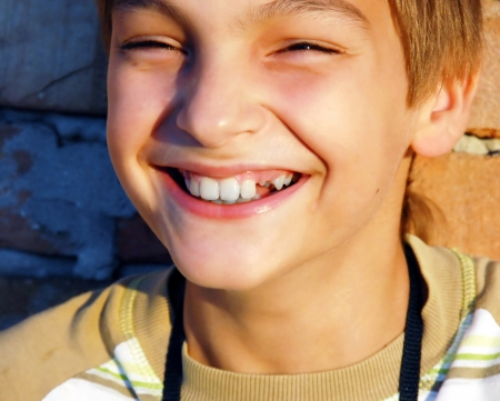 sincerely: laughing teen caucasian boy with missing tooth portrait
