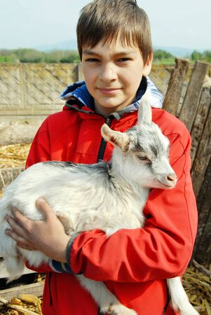 teenage boy portrait outdoors with little goat in hands photo