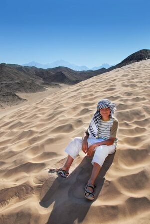 teenage smiling caucasian boy tourist sitting on sand dune in Egypt Stock Photo - 9647726