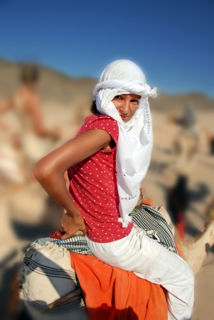 bedouin: girl tourist in white kerchief riding camel in egypt