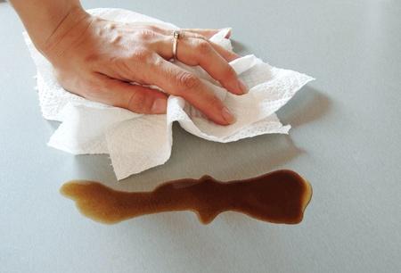 Frau Hand abwischen verschüttet Kaffee mit Küchenpapier