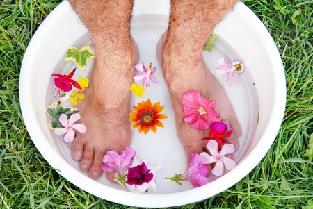 male hairy feet in bowl with water and flowers photo