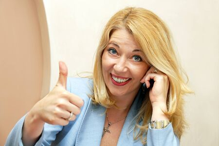 blond smiling businesswoman with mobile phone showing ok sign Stock Photo - 9703006