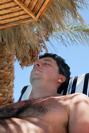 hairy chest: caucasian man portrait lying under sunshade on beach in Egypt