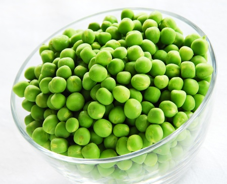 peas: young fresh green spring peas in glass bowl