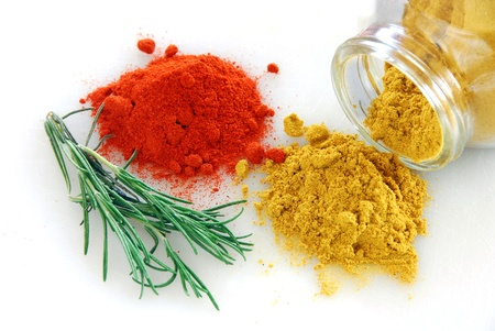 red paprika and curry heaps with rosemary branch on white background Stock Photo