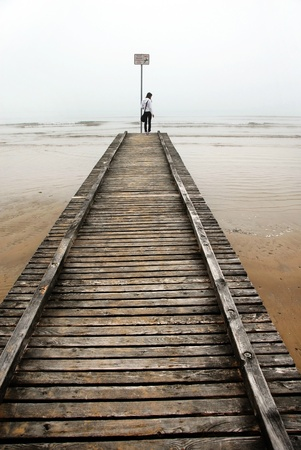 spring tide: teenage girl standing on old sea pier, Italy