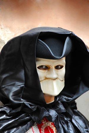 stranger: portrait of male adult doll in scary mouthless mask on street in Venice, Italy