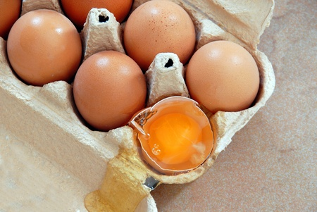 brown eggs in cardboard box, one broken egg closeup photo