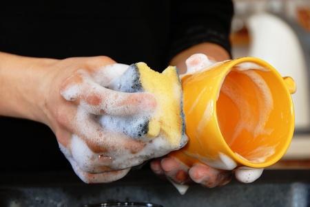 lavar trastes: manos con esponja de lavar los platos en el fregadero de la cocina