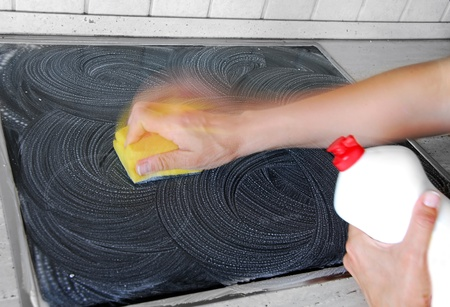 house chores: hand with a sponge cleaning surface in kitchen