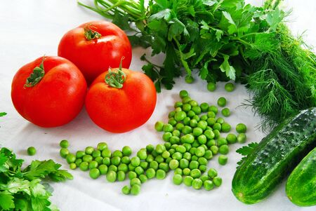scattered: fresh appetizing vegetables on table, red tomatoes, spring peas, parsley and cucumber Stock Photo