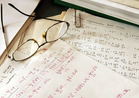 glasses over physics formulas and calculations written on paper
