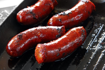 appetizing red roast sausages on frying pan photo