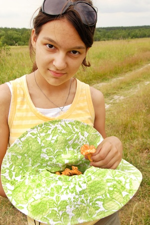 portrait of young smiling teenage caucasian girl outdoors with chanterelle mushrooms photo