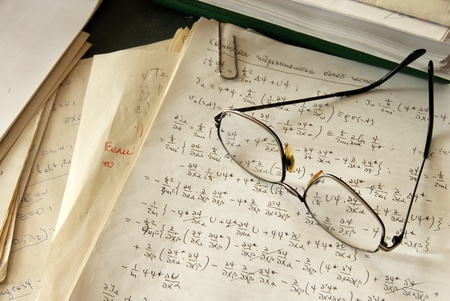 glasses over physics formulas and calculations written on paper photo