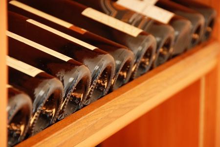 various wine bottles in row on wooden shelf