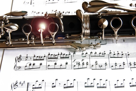Fragment of black shining clarinet over opened music book