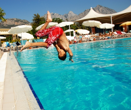 sky dive: boy jumping into blue swimming pool in resort