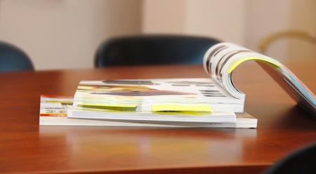 opened magazines on brown business desk indoor