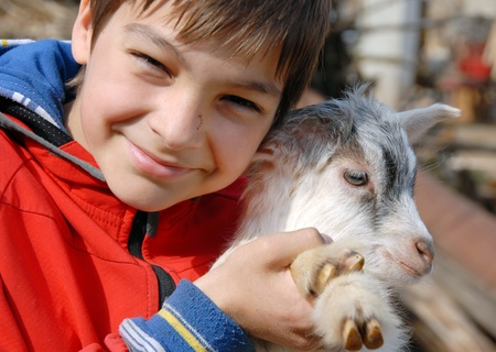 yeanling: teenage boy portrait with young white goatling smiling outdoor