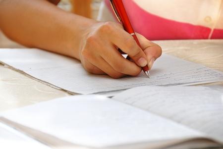 schoolgirl with pen writing down in notebook homework Standard-Bild