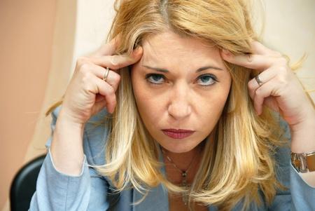 agotado: empresaria rubia que sufren de dolor de cabeza retrato en interiores
