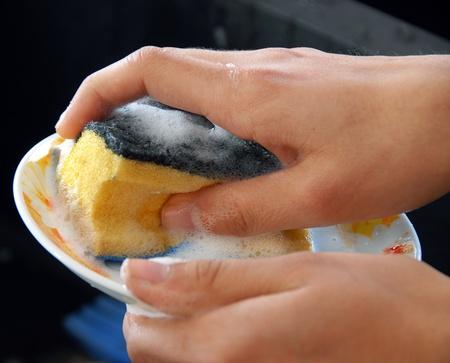 hands with sponge washing dishes in kitchen sink Standard-Bild