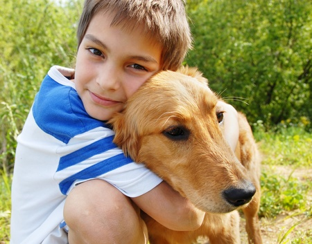 happy smiling little boy hugging his golden retriever dog closeup